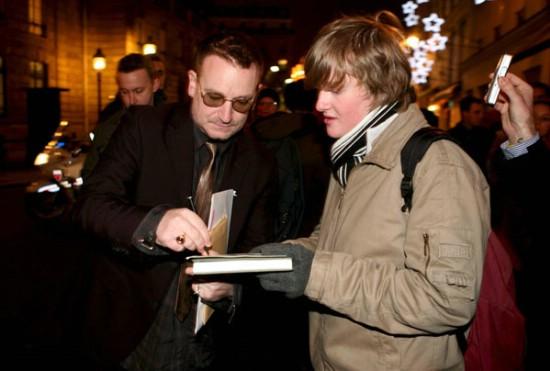 Bono de U2 dando su rúbrica